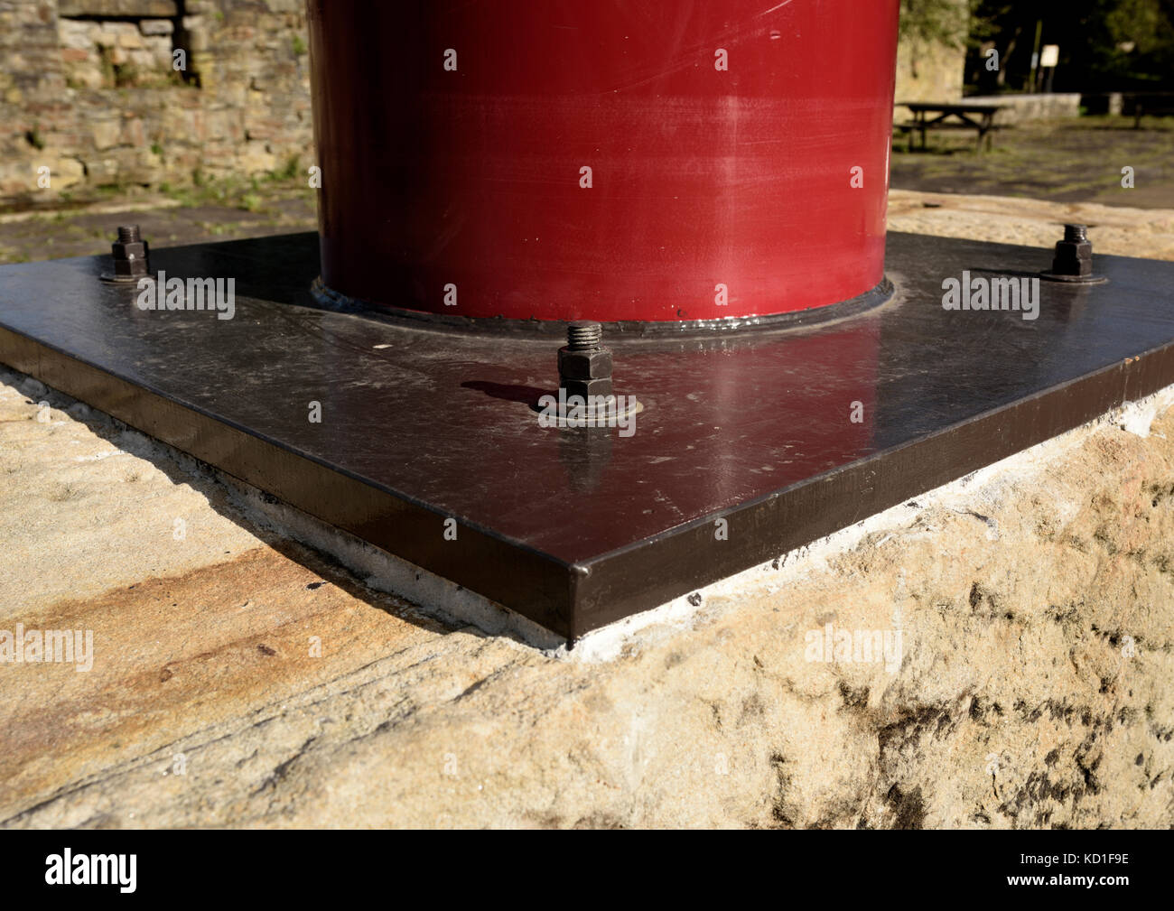 Steel plate at base of sculpture fixed  to stone block with anchor bolt fixing at burrs country park in bury lancashire - Stock Image
