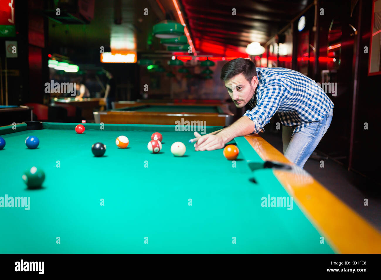 Hansome man playing pool in bar alone - Stock Image