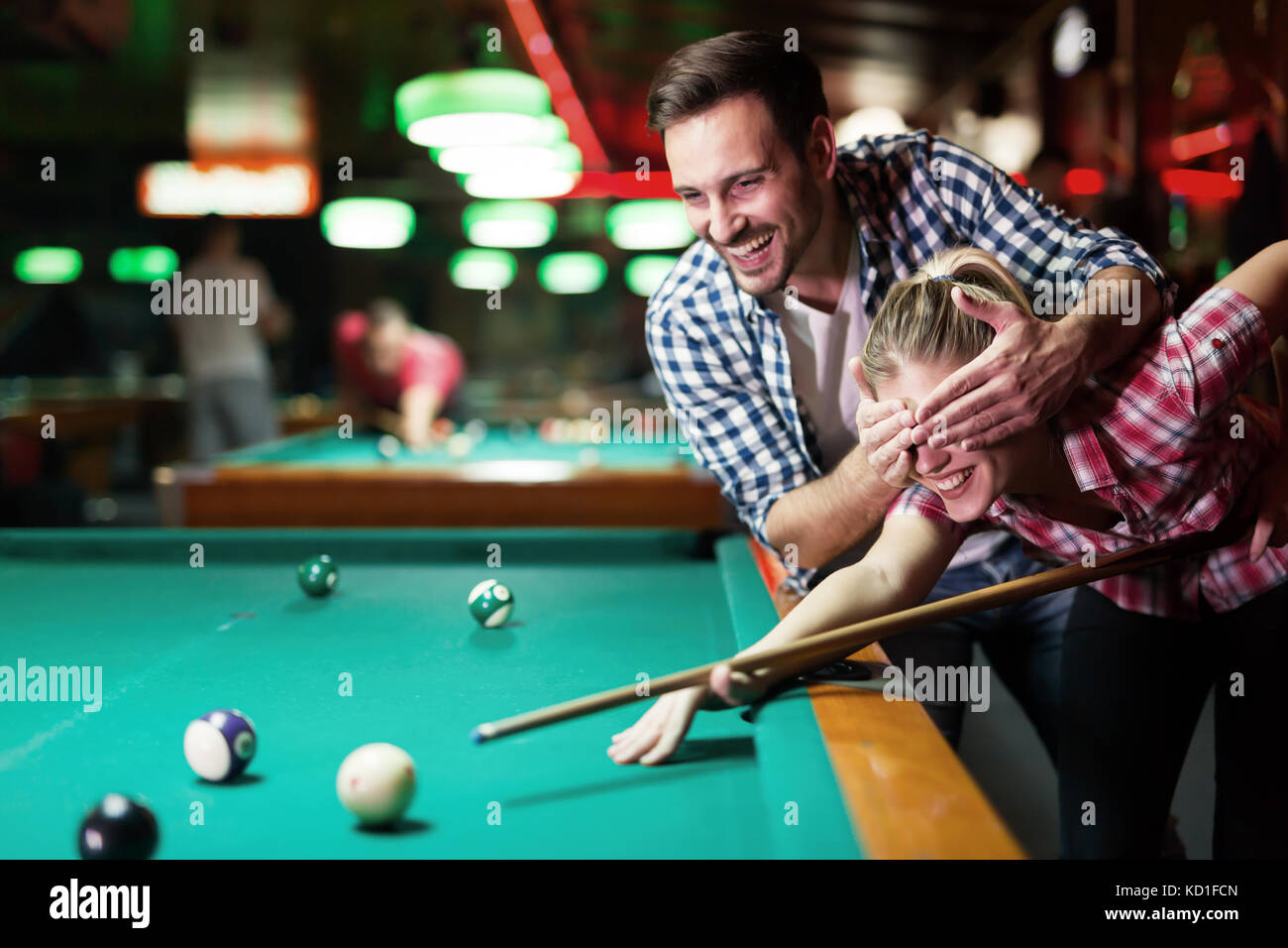 Young couple playing together pool in bar - Stock Image