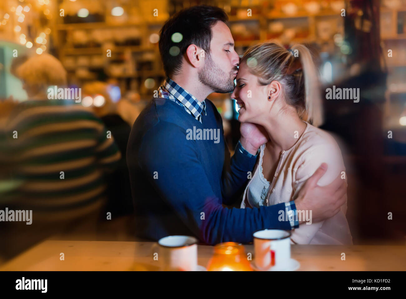 Happy couple kissing at bar and having date - Stock Image
