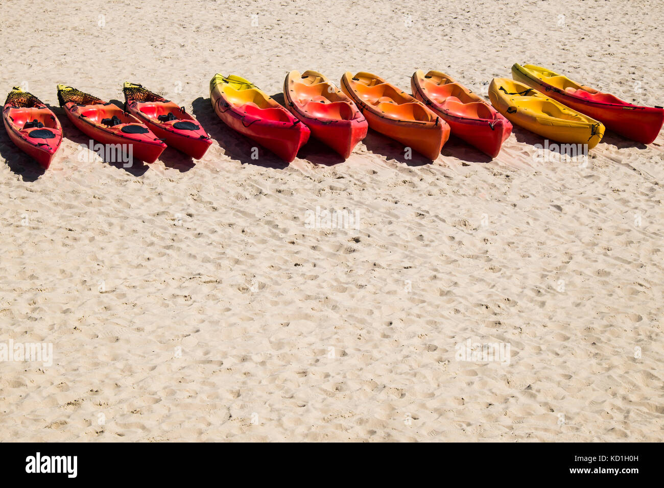 Hire canoes lined up on a beach looking well used at the end of the season. Stock Photo