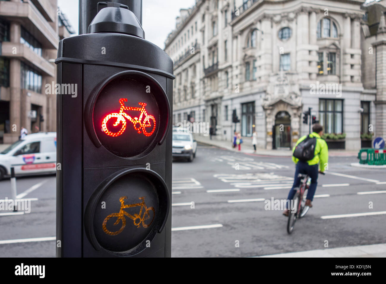 Cyclist cycles through a red light. City of London, UK - Stock Image