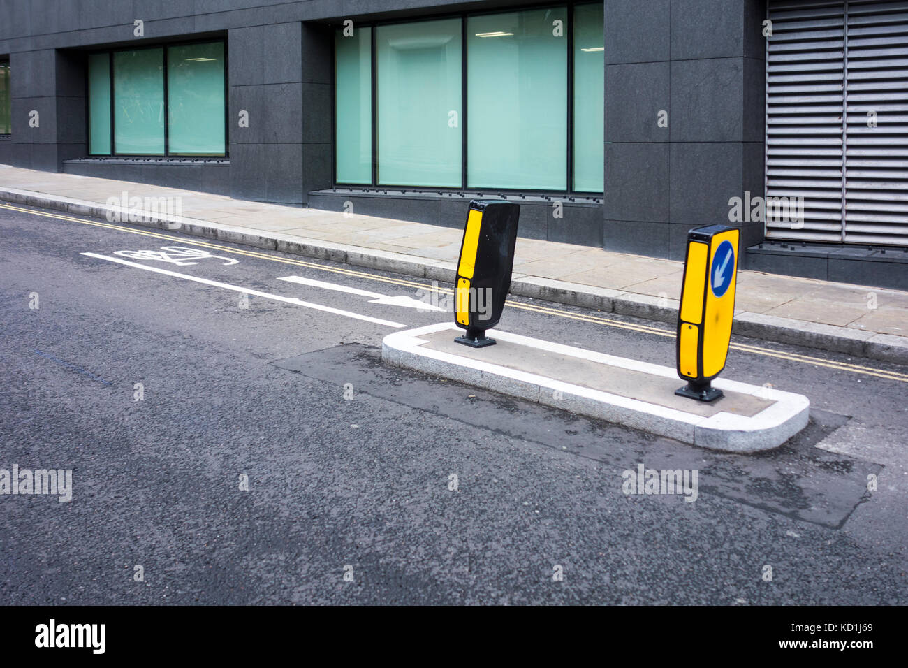 Central road bollard next to separated dedicated cycle lane. Lambeth Hill, London, UK - Stock Image