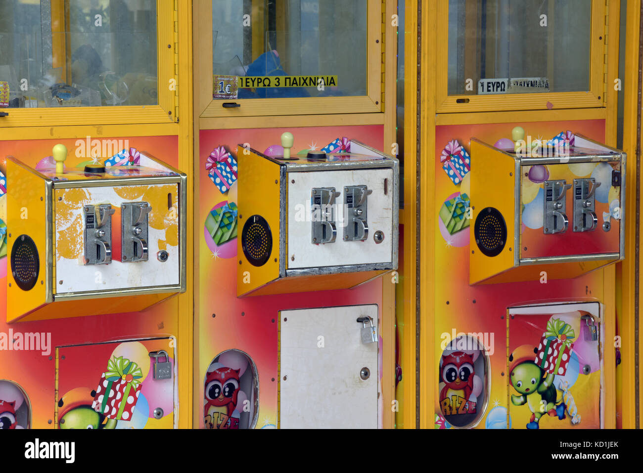 yellow or brightly painted coin mechanisms on amusement arcade machines . coin operated vending or amusement gifts - Stock Image