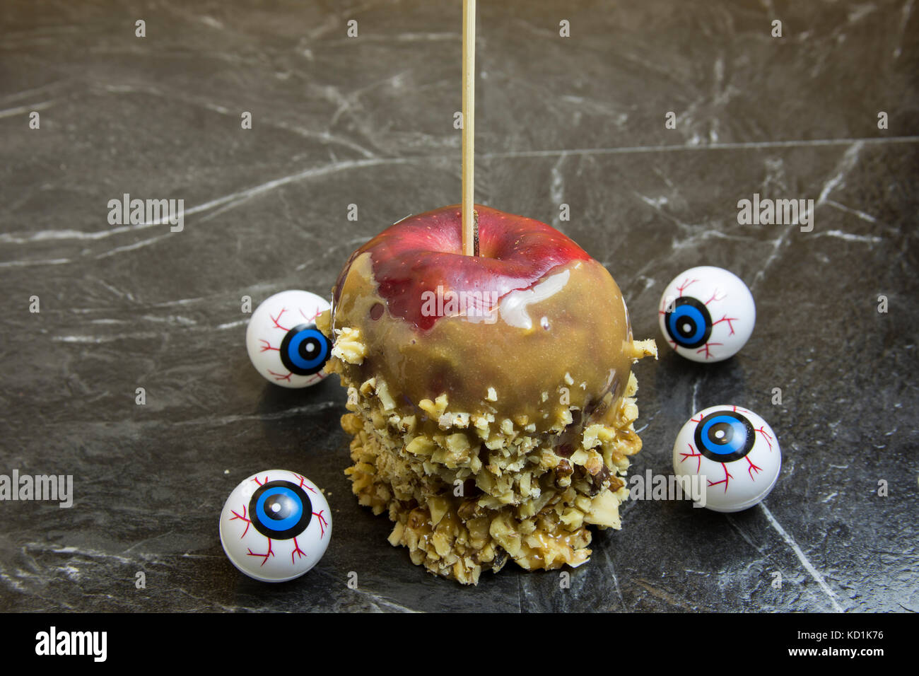 Caramel dipped red apples coated with chopped walnuts surrounded by eyeballs. - Stock Image