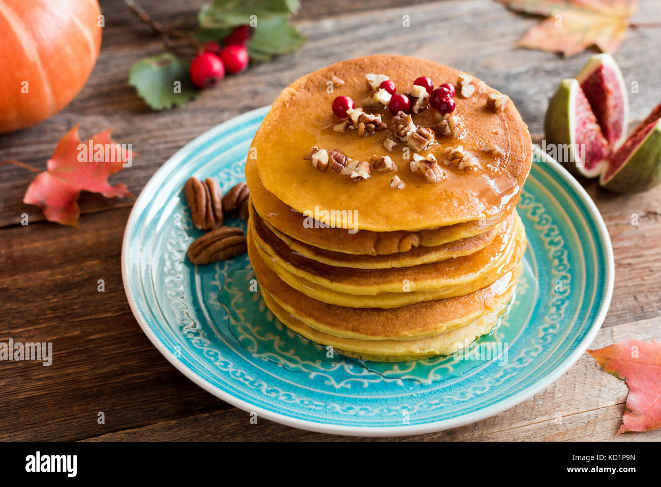 Pumpkin pancakes with pecan nuts, red berries and honey on a blue turquoise plate. Seasonal autumn food Stock Photo