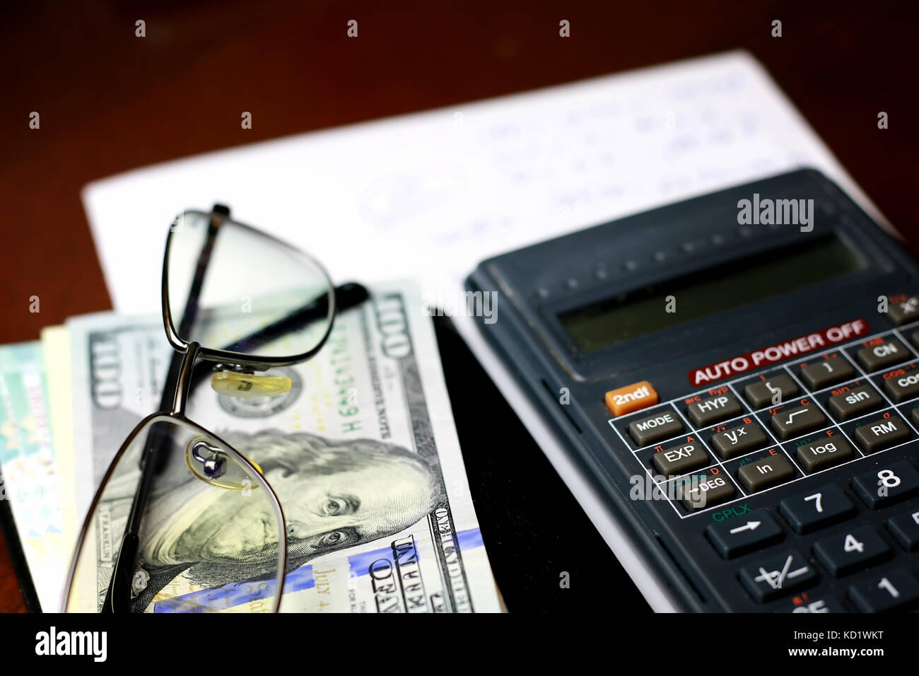 calculator on the table glasses money - Stock Image