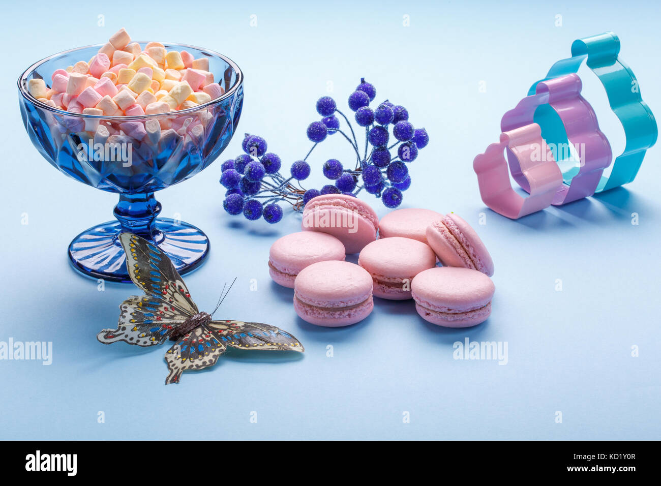 Macaroon cakes with colorful fluffy marshmallows in blue vase over blue background. - Stock Image
