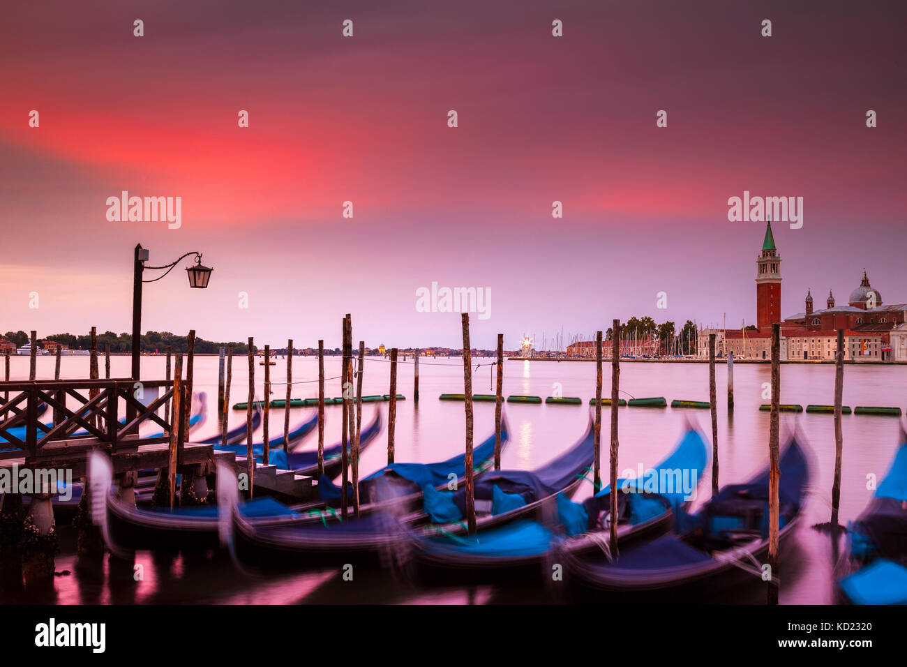 Dramatic sunrise over Venice, Italy.  In the foreground are the iconic gondolas and across the canal is the island Stock Photo
