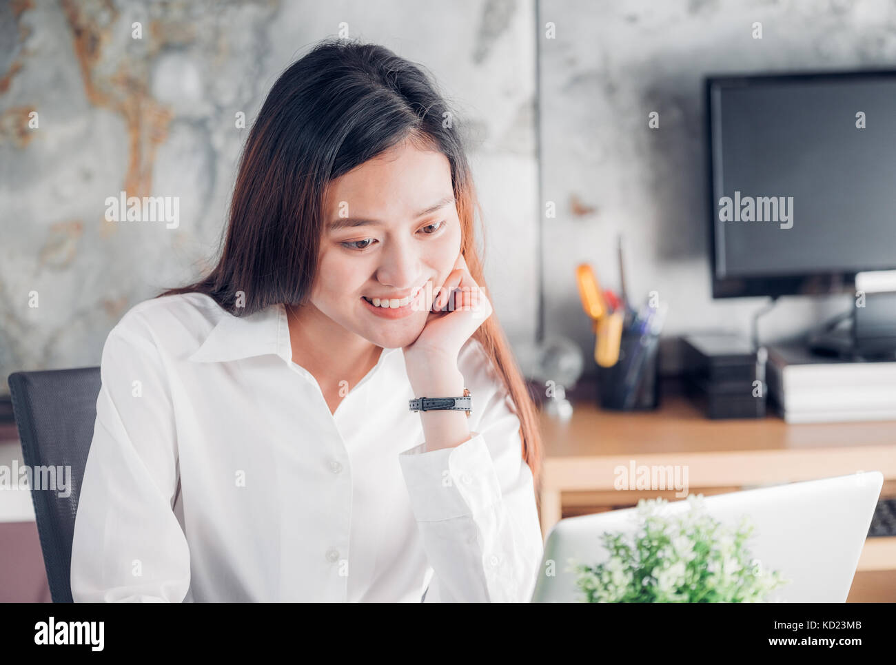 Asian businesswoman looking at laptop computer and smiling face and rest chin on hand with happy emotion from good - Stock Image