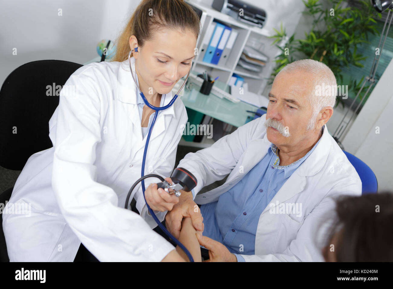 male doctor explaining apprentice how to messure pressure - Stock Image