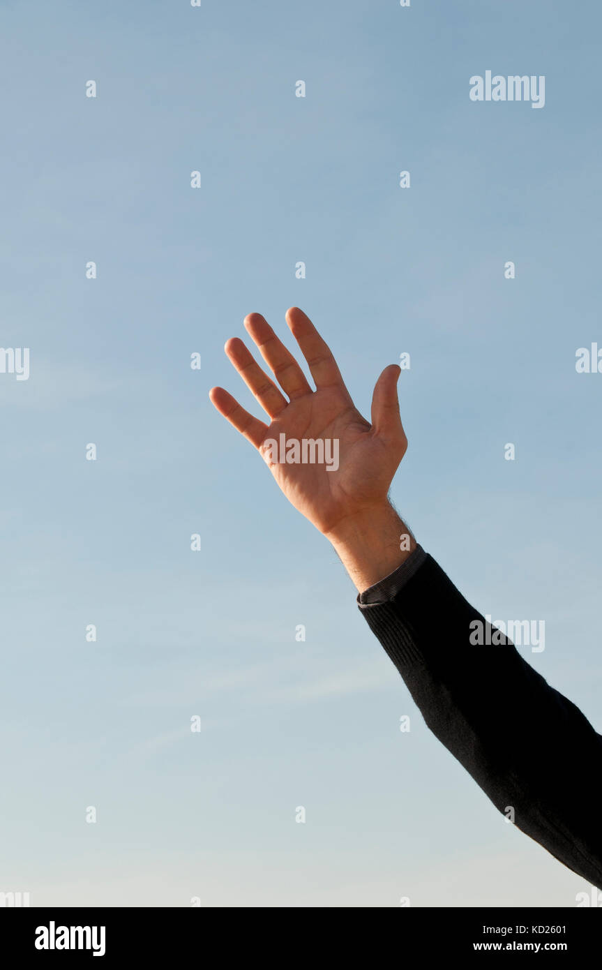 Close up of a man's hand waving goodbye outdoors - Stock Image