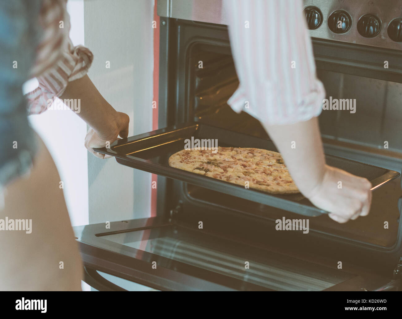 Woman preparing pizza bought in a store. - Stock Image