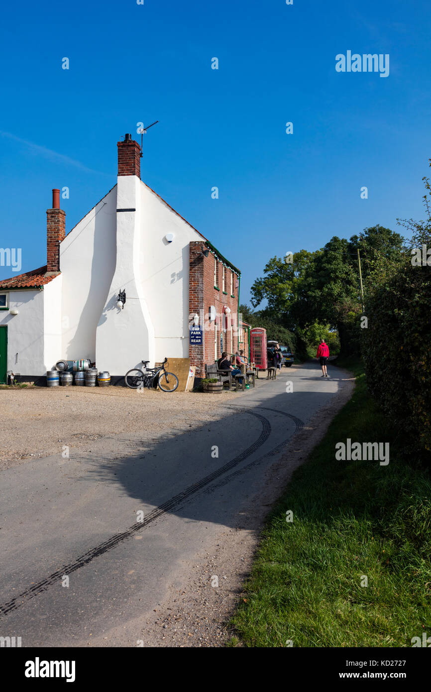 A traditional Norfolk pub near Horsey, The Nelson Head, with a red telephone box outside and customers on benches, - Stock Image