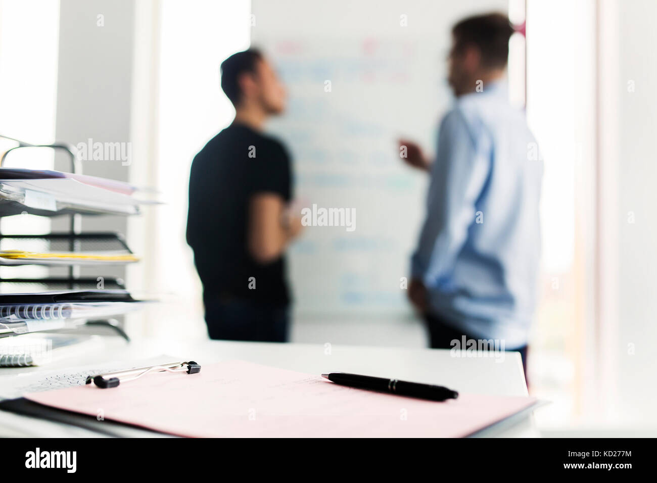 Clipboard with pen, colleagues in background - Stock Image
