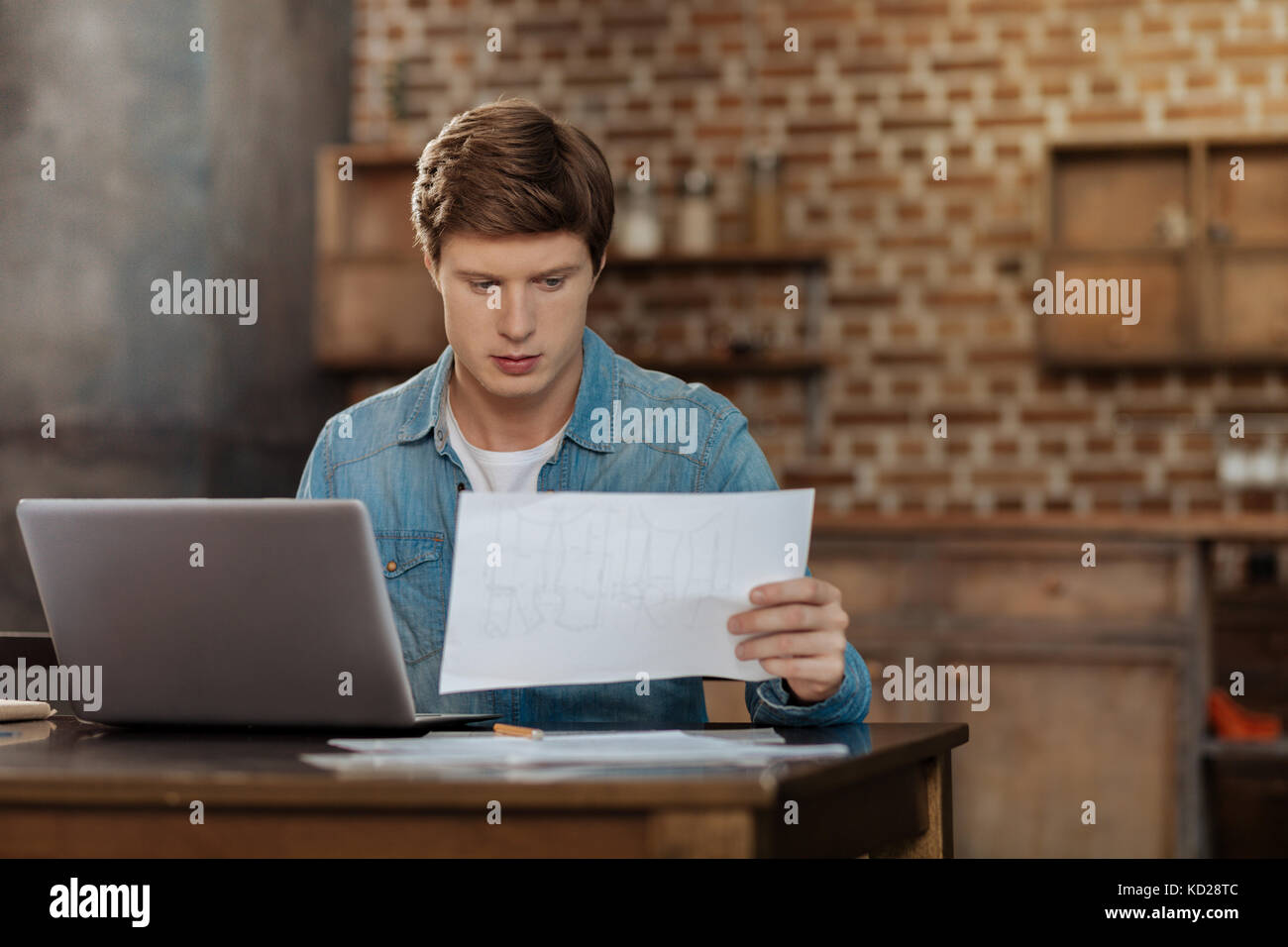 Handsome young man studying the blueprint - Stock Image