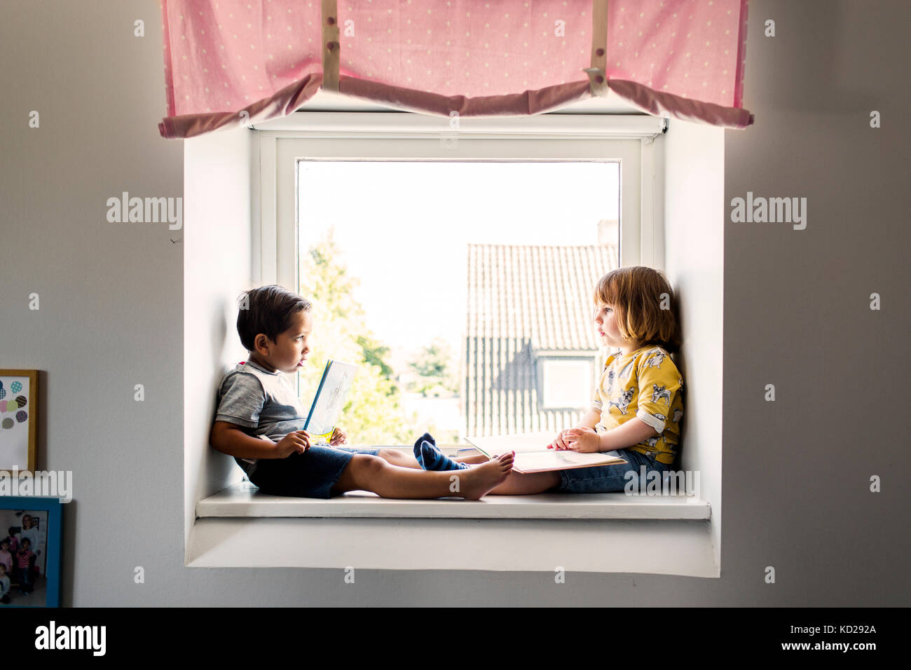 Girl and boy (2-3) sitting and reading by window - Stock Image