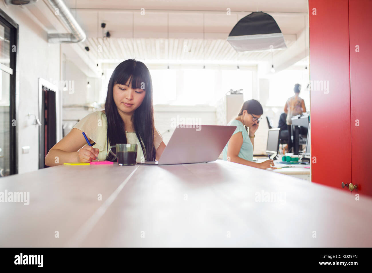 Two women working at office, third standing by window in background - Stock Image