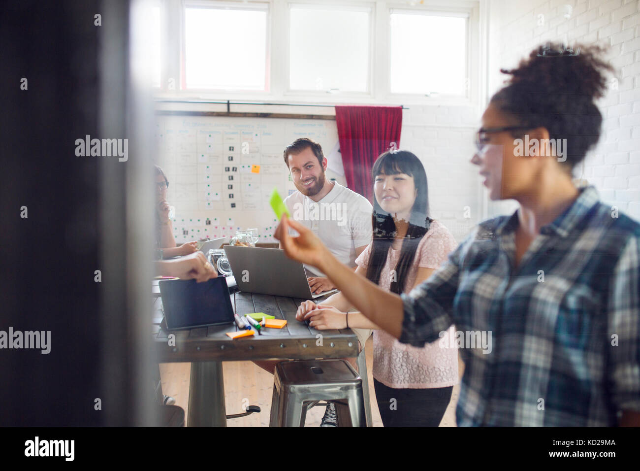 Smiling coworkers in office, woman gesturing - Stock Image