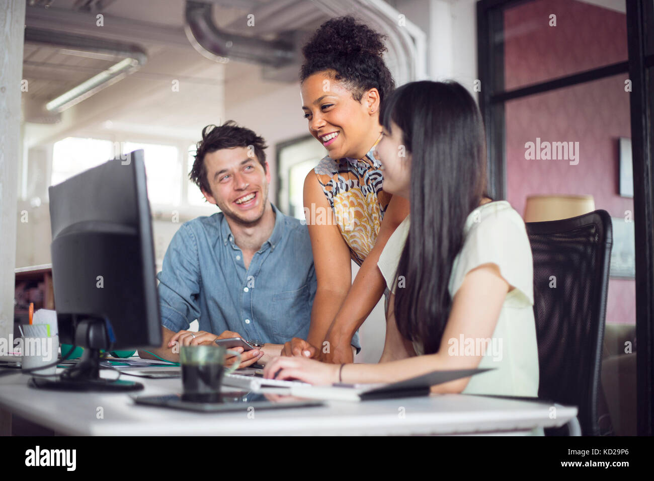 Coworkers smiling in front of computer monitor Stock Photo