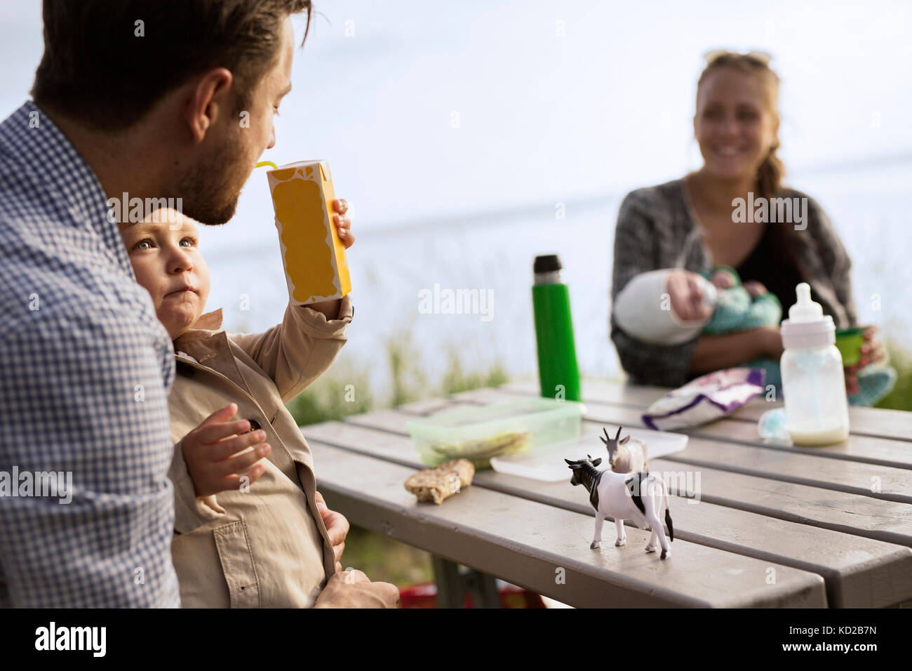 Father sitting with son (18-23 months) by picnic table - Stock Image