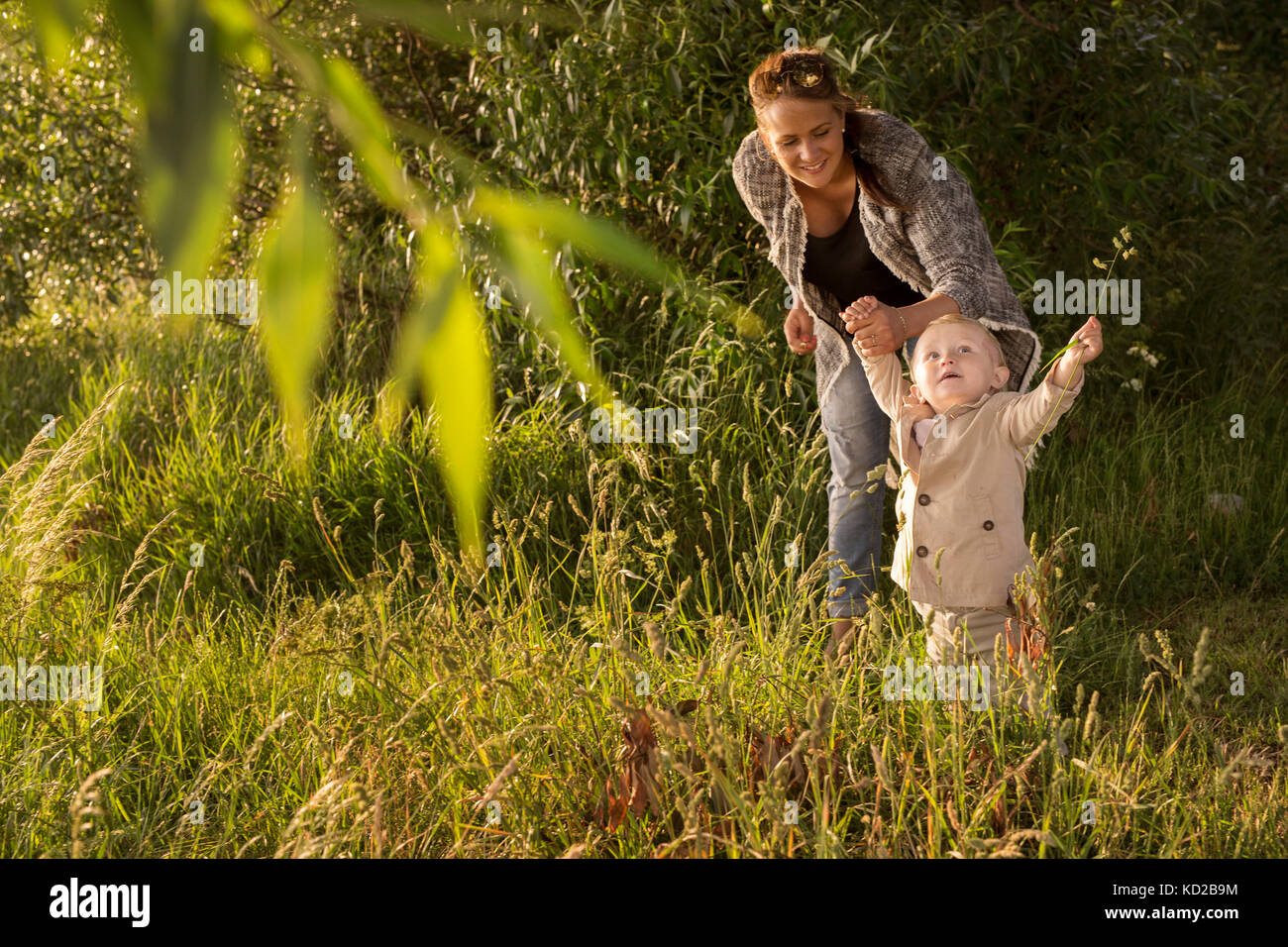 Mother with son (18-23 months) standing by tree Stock Photo