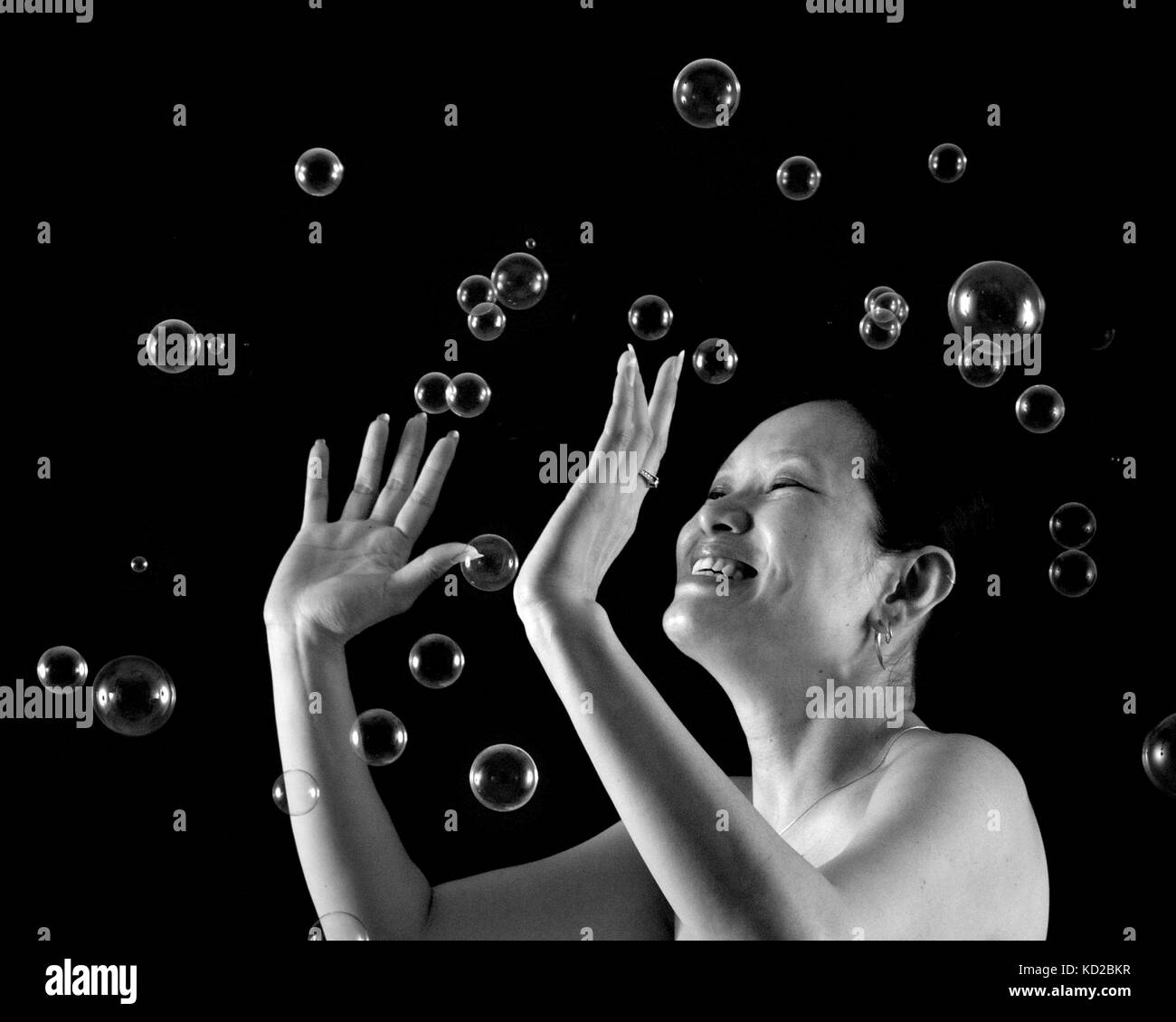 Chinese woman playing with blow bubbles - Stock Image