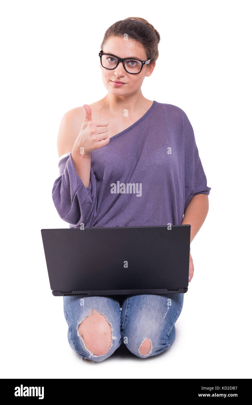 Young student girl studying and using a laptop while rising thumb up - Stock Image