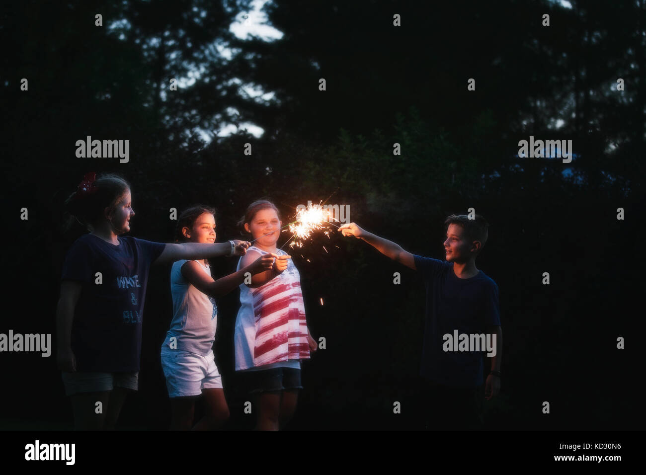 Boy and three girls igniting sparklers together at night on independence day, USA - Stock Image