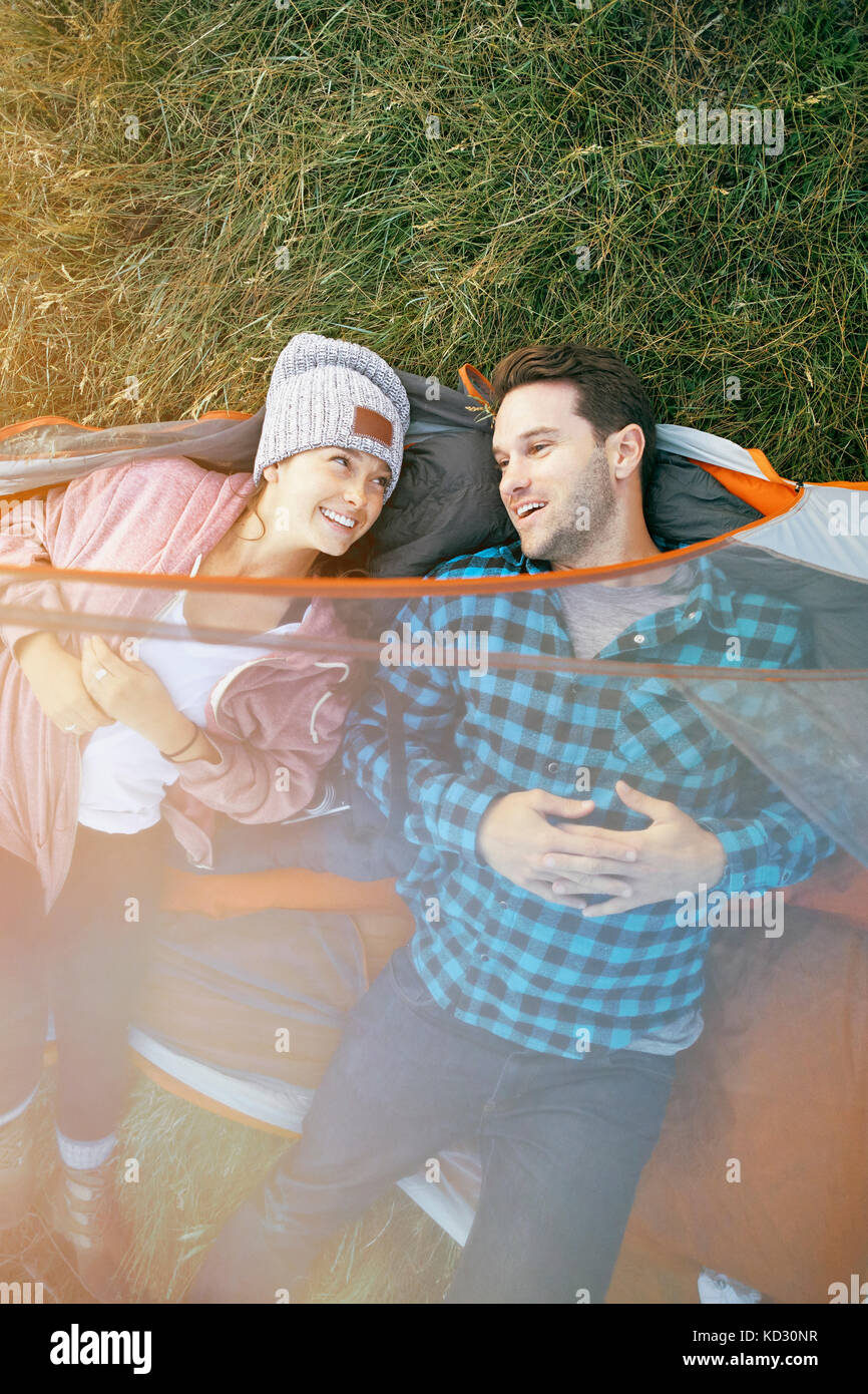 Couple lying in tent, heads outside of tent, smiling, overhead view - Stock Image