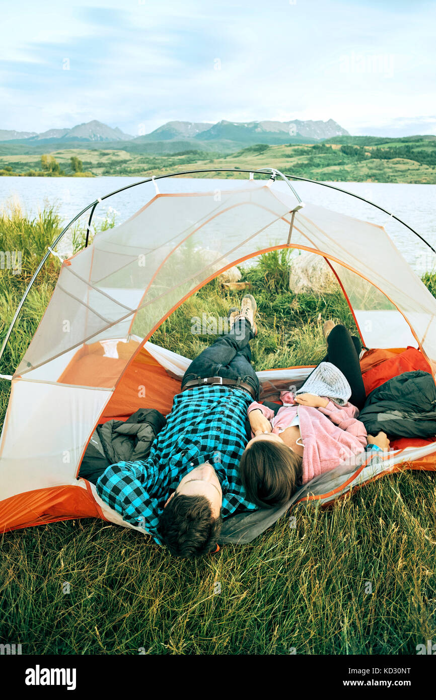 Couple lying in tent, heads outside of tent, rear view, Heeney, Colorado, United States - Stock Image