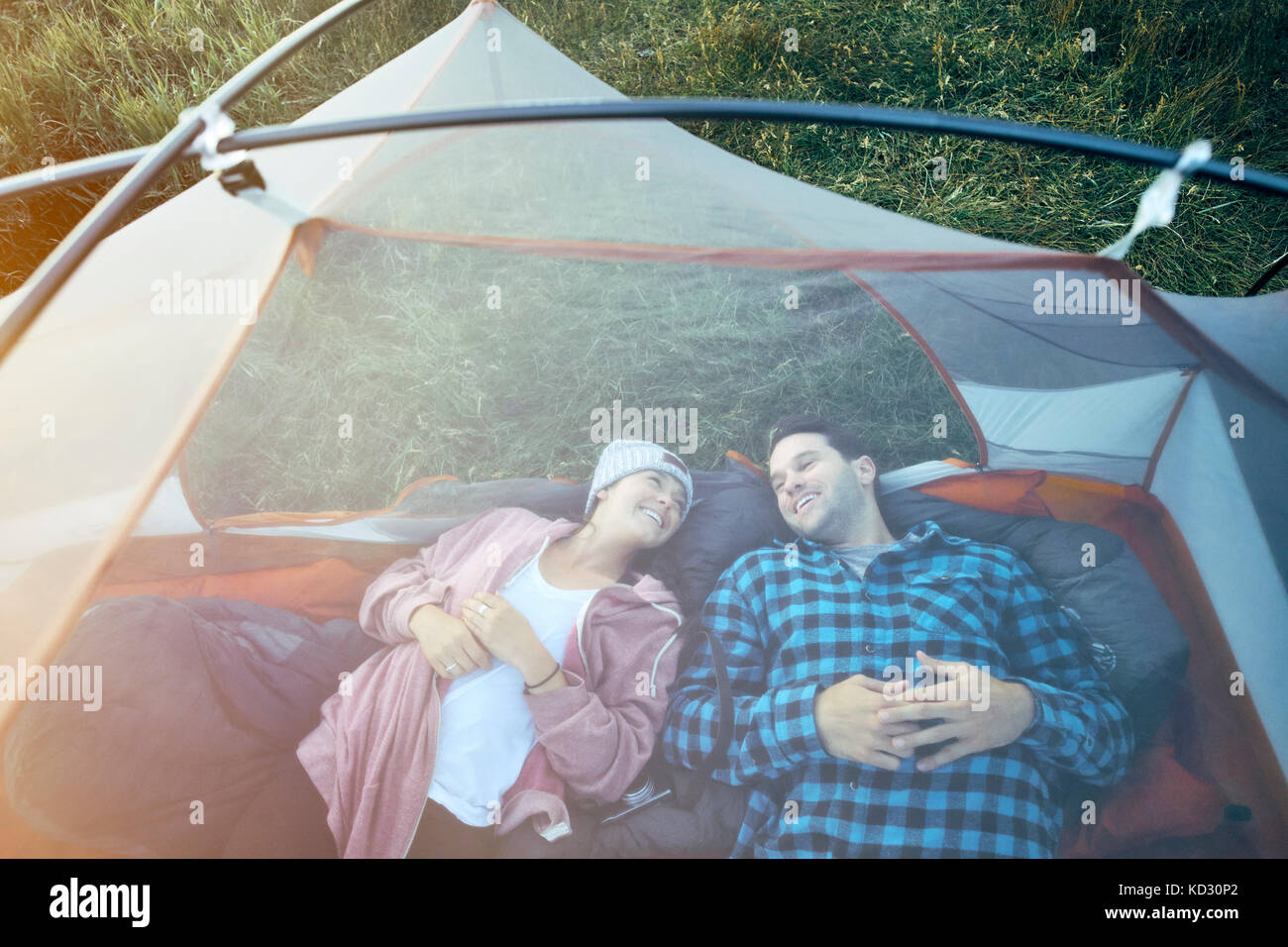 Couple lying in tent, elevated view - Stock Image