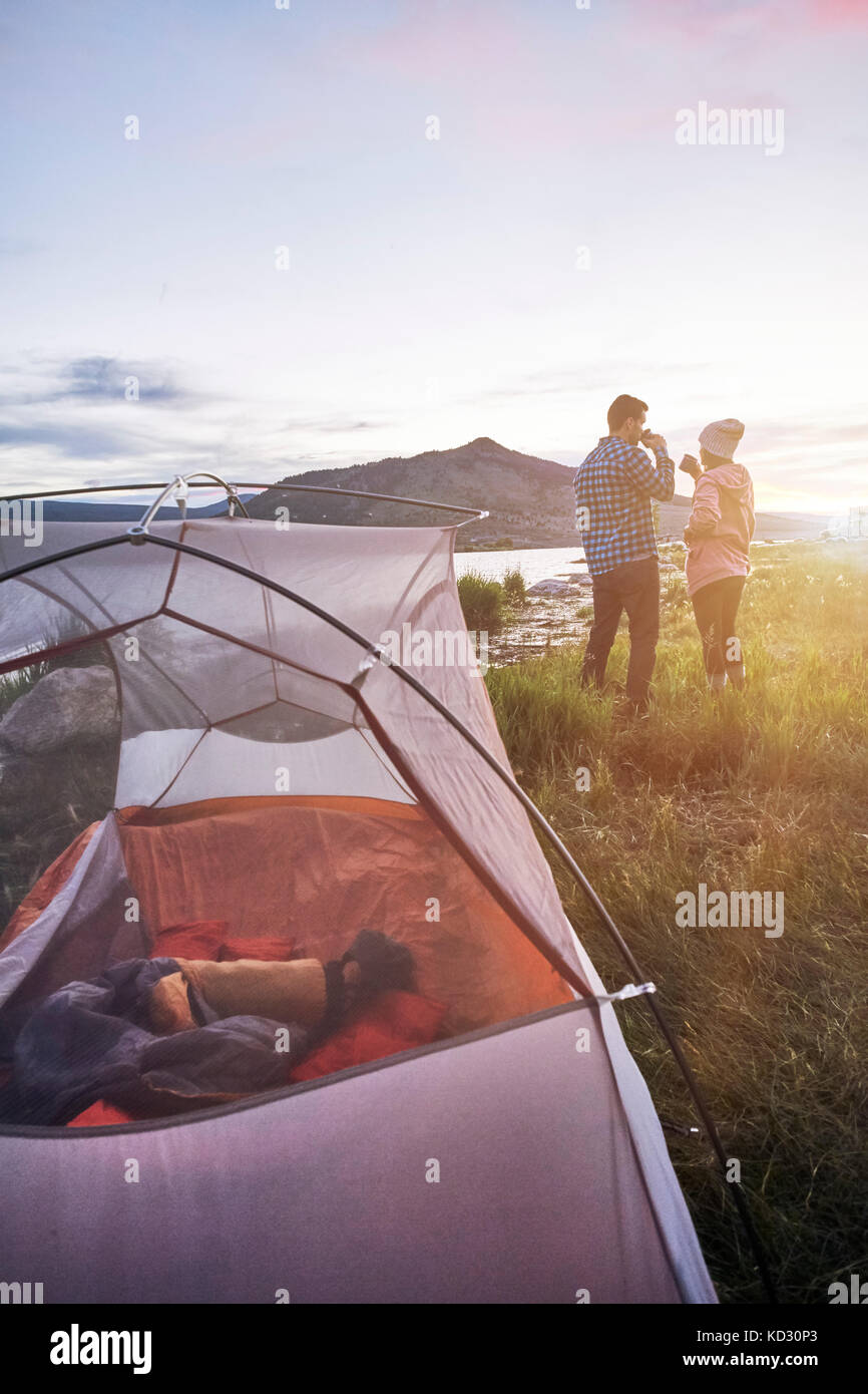 Couple standing near tent, drinking hot drinks, looking at view, Heeney, Colorado, United States - Stock Image