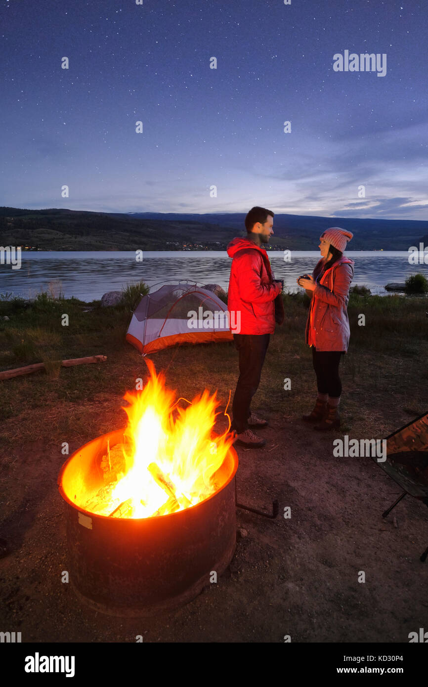Couple standing near tent and campfire. at dusk, drinking hot drinks - Stock Image