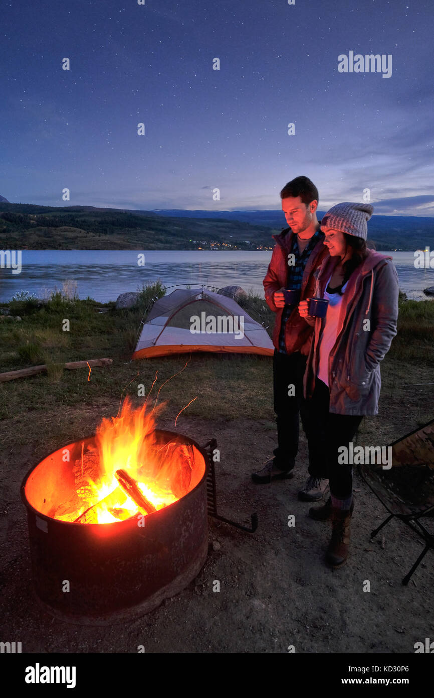 Couple standing near campfire. at dusk, drinking hot drinks - Stock Image