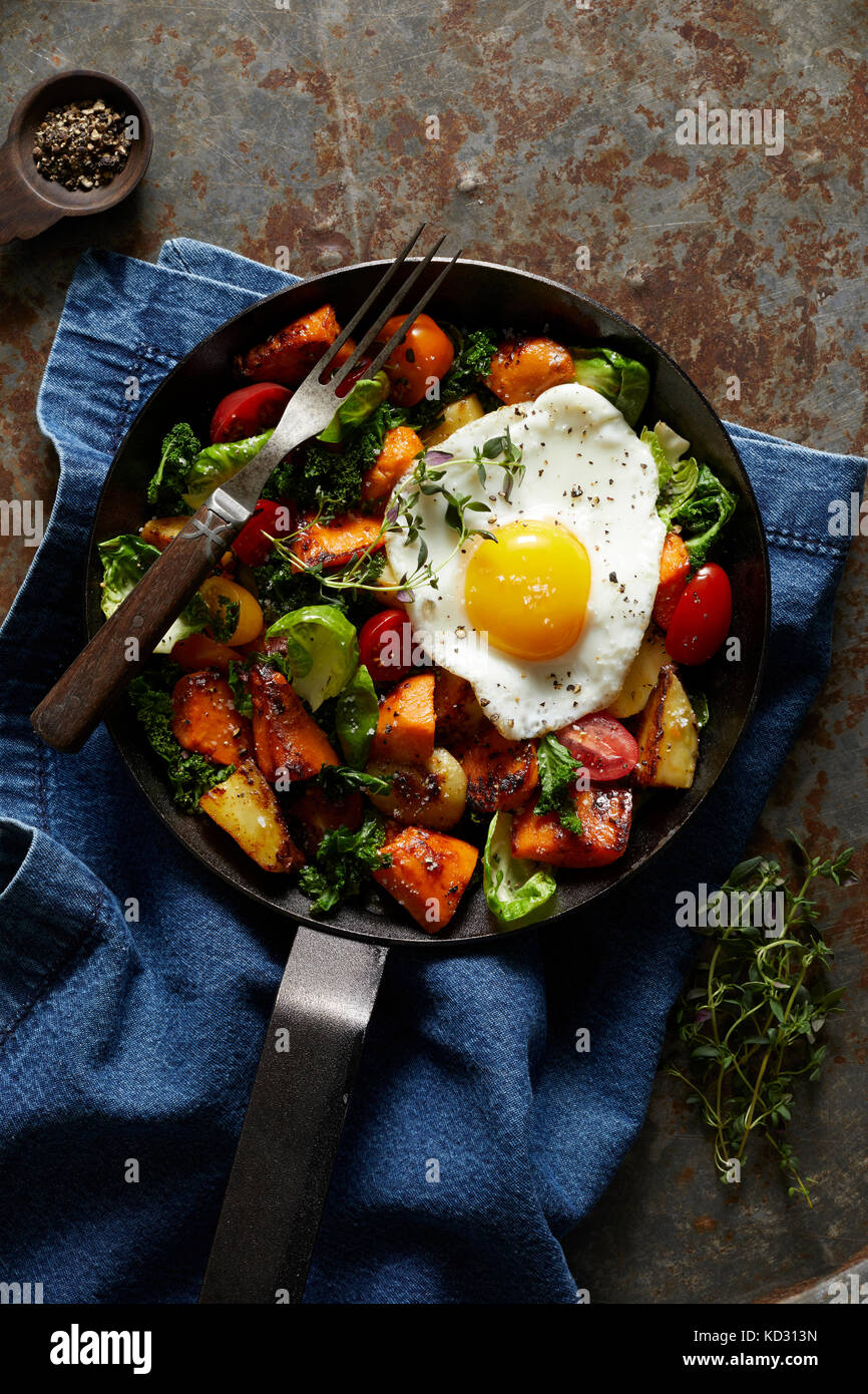Breakfast hash with fried egg in cast iron skillet - Stock Image