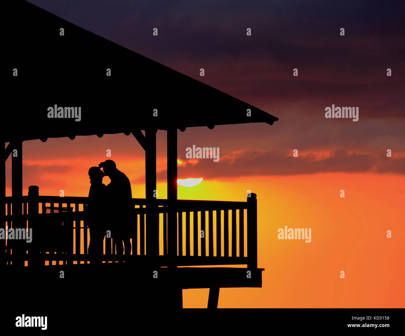 Lovers silhouetted against the sunset on a deck steals a romantic kiss in landscape format with copy space - Stock Image