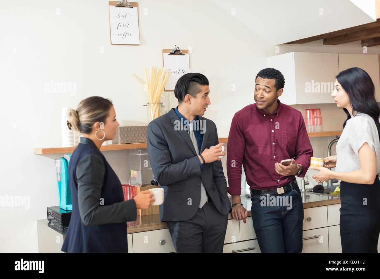 Businesswomen and men having informal meeting in office kitchen - Stock Image