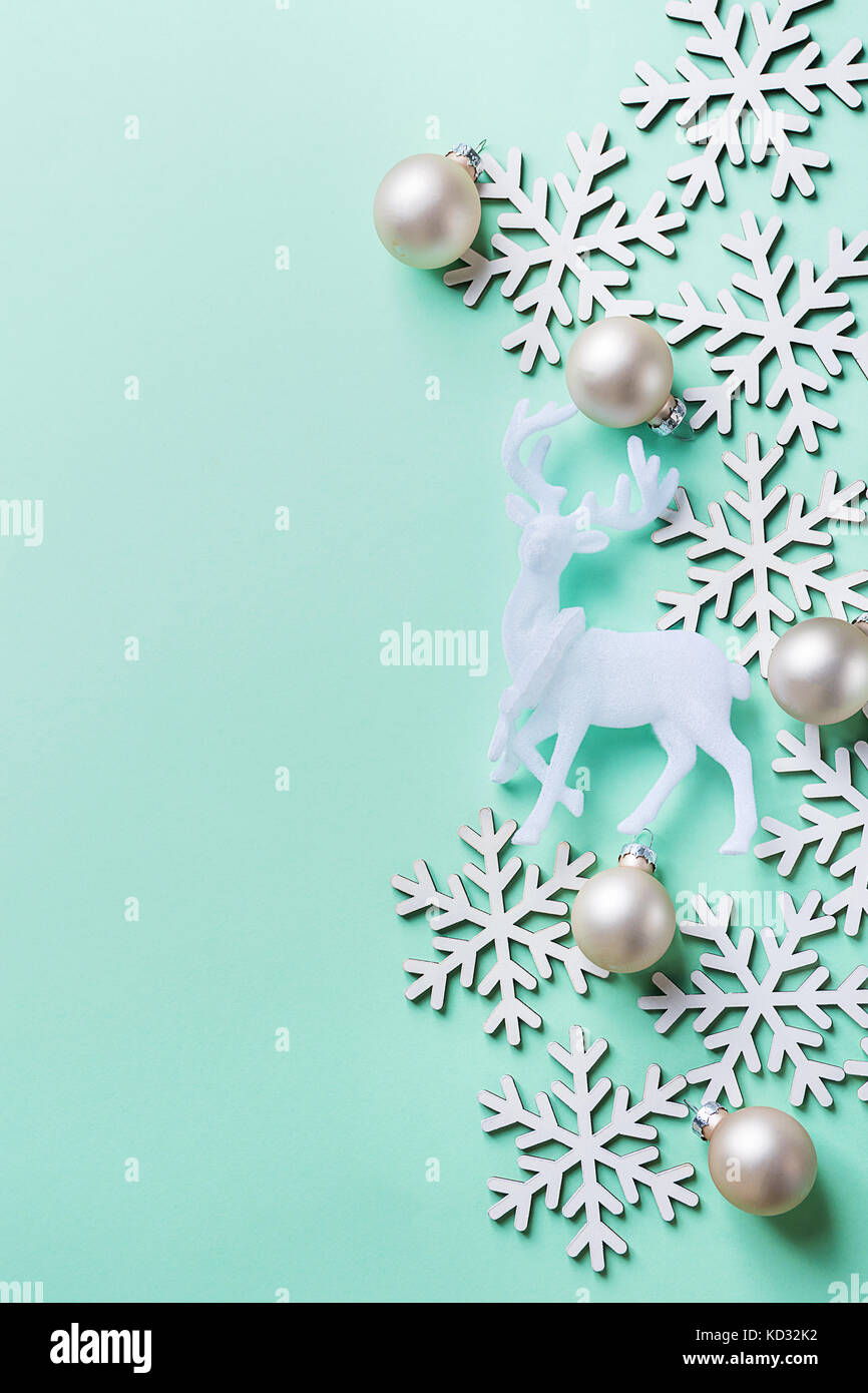 Elegant Christmas New Year Greeting Card Poster White Reindeer Snow Flakes Ball on Light Turquoise Blue Background. - Stock Image