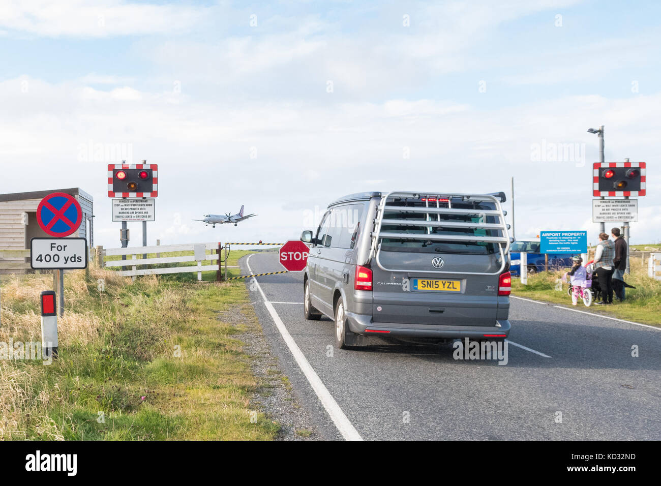 Sumburgh Airport - plane coming in to land on runway that is crossed by a road controlled by a level crossing, Shetland - Stock Image