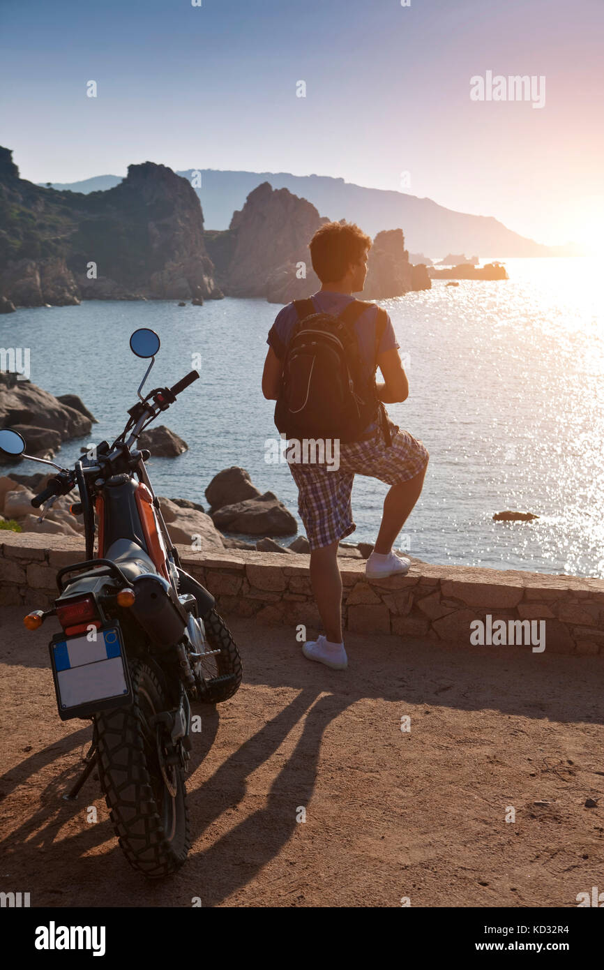 Man with motorbike looking away at view of sunset over sea, Olbia, Sardinia, Italy - Stock Image