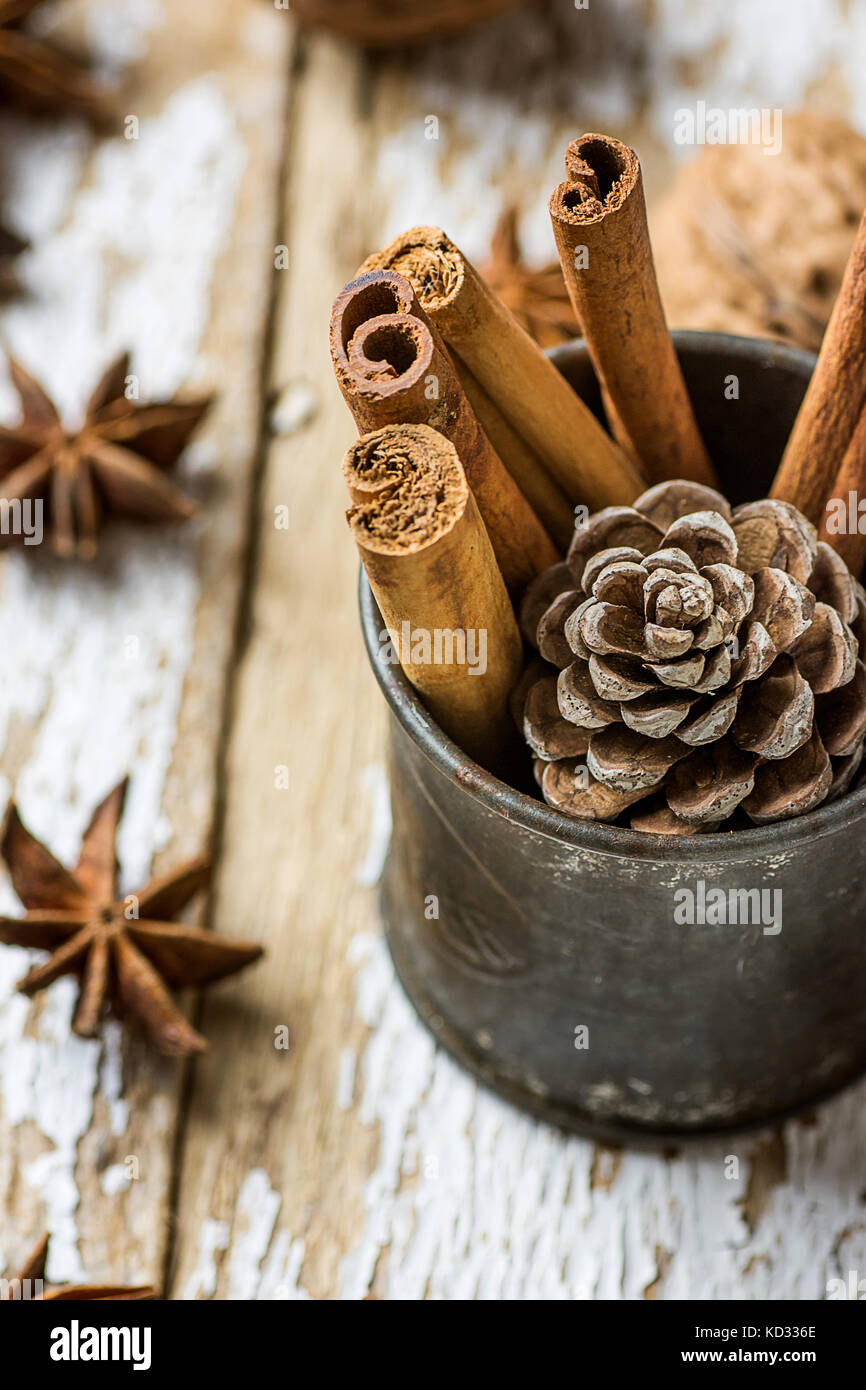 Christmas Baking Ingredients Cinnamon Sticks Scattered Anise Star Walnuts Pine Cone in Vintage Jug on Wood Background. - Stock Image