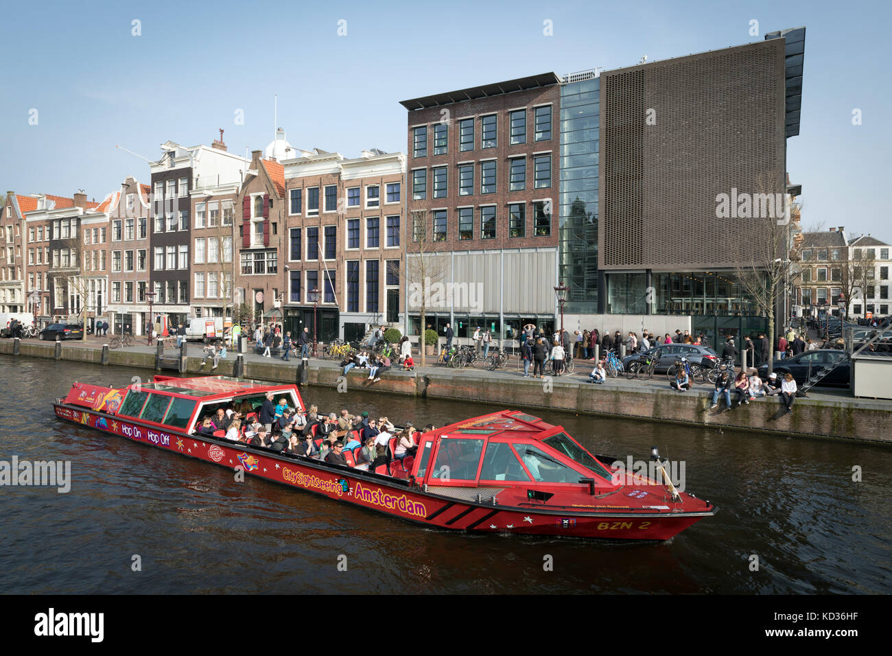 A tourist boat on the Prinsengracht canal sails past the Ann Frank House in Amsterdam - Stock Image