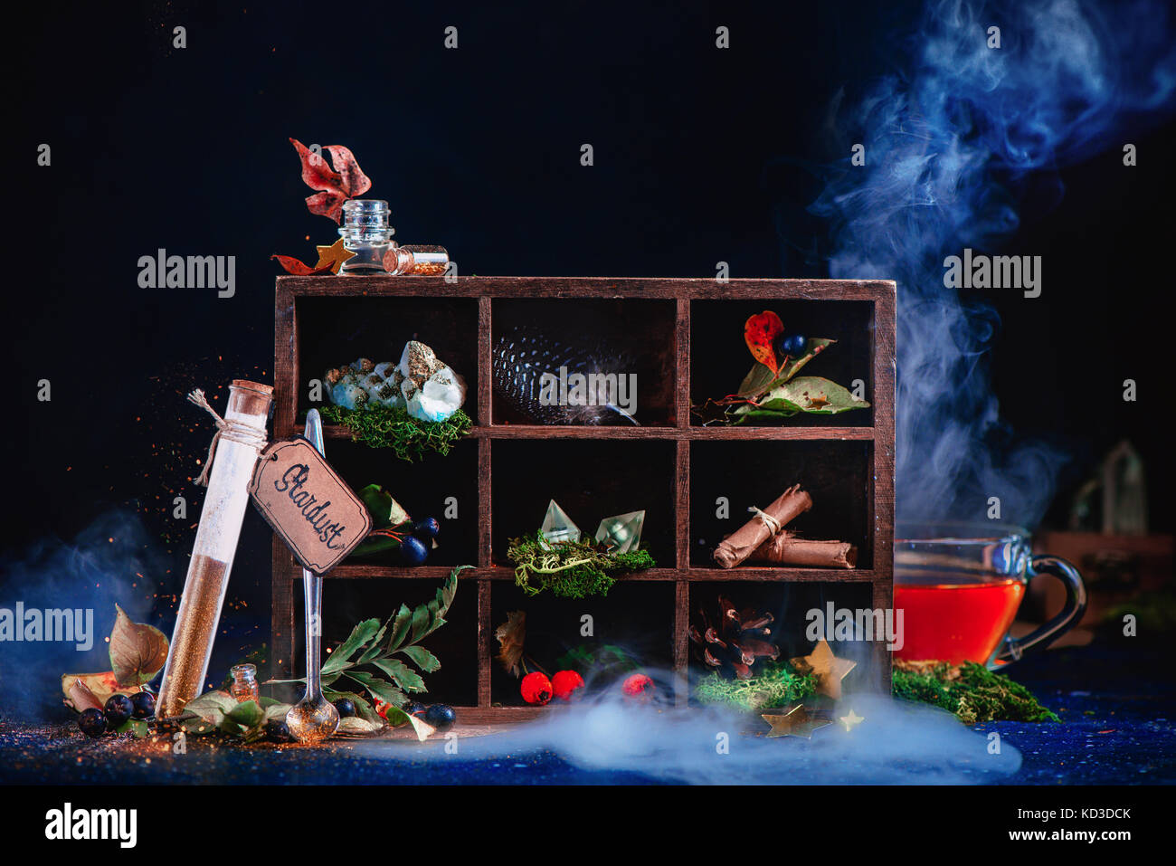Shining test tube with pixie dust. Steaming cup of tea in a magical still life with potion ingredients, berries, feather, scrolls, crystals and a wood Stock Photo