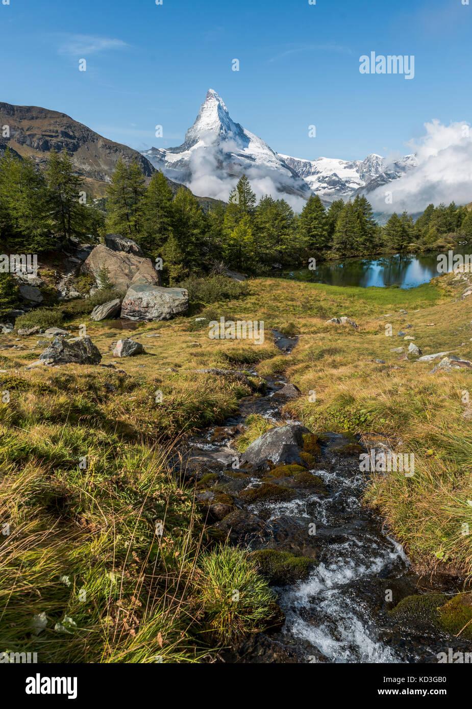 Snow-covered Matterhorn, stream flows into the Grindijsee, Valais, Switzerland - Stock Image