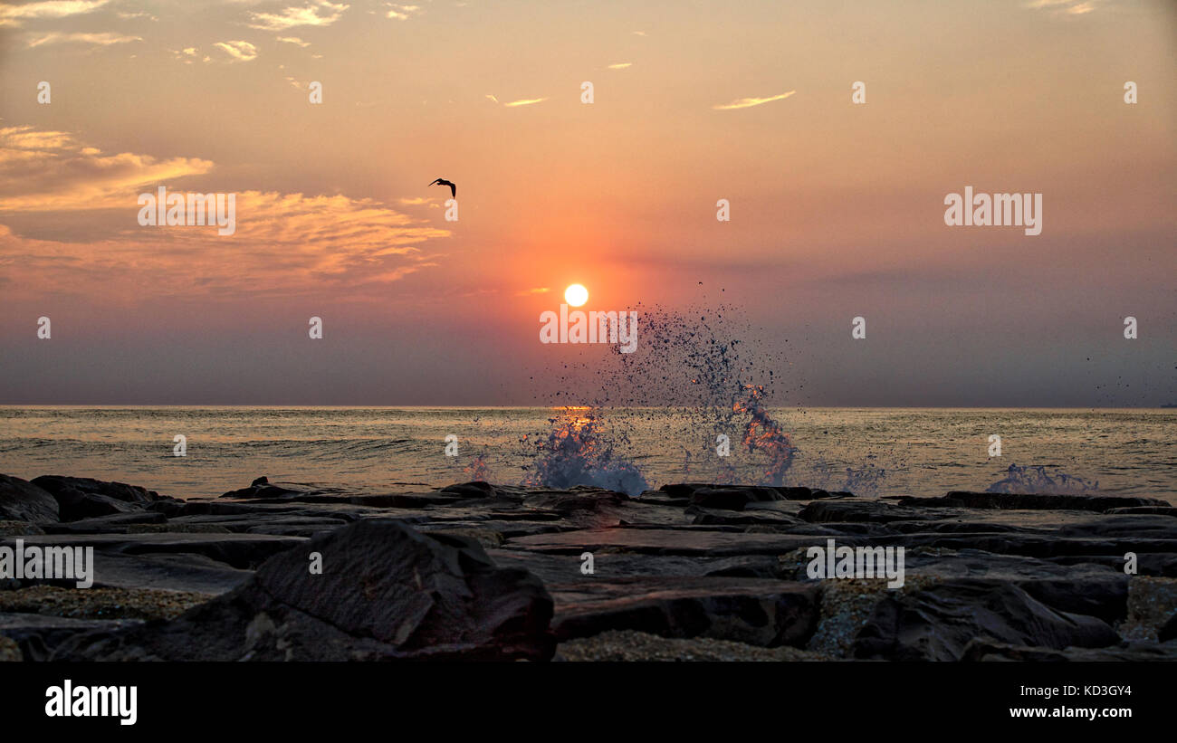 A splash of water coming off the jetty as the sun comes up over the horizon. - Stock Image
