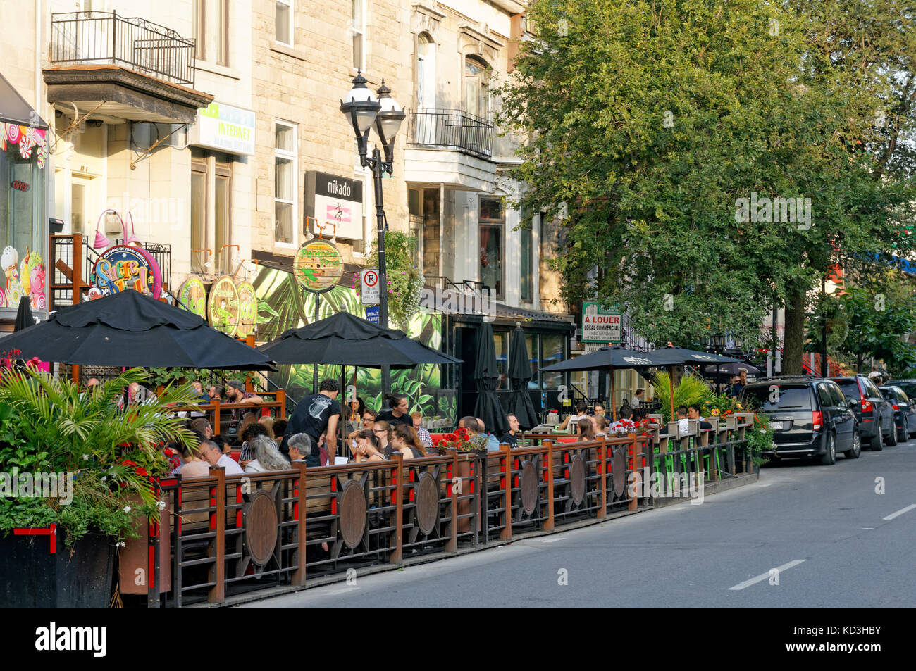 People sitting and talking in outdoor restaurants and bistros on Rue Saint Denis street, Latin Quarter, Quartier - Stock Image