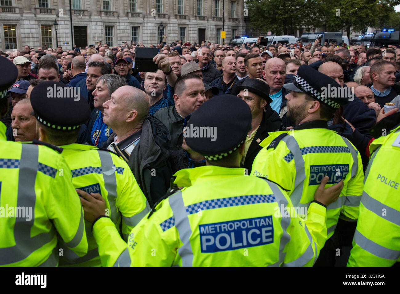 London, UK. 7th October, 2017. Supporters of the Football Lads Alliance move past anti-racist campaigners from Stand - Stock Image