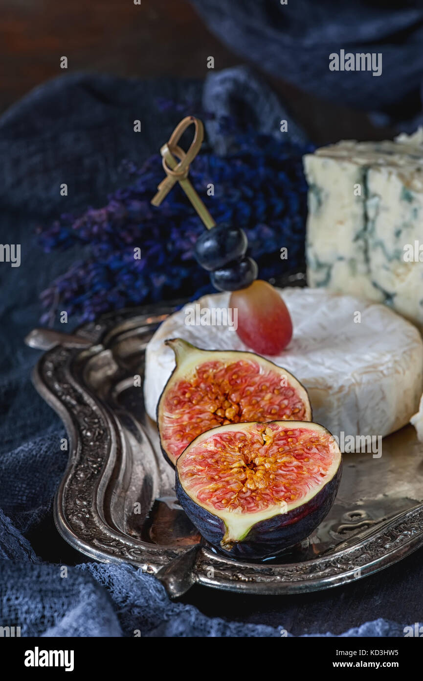 Half of ripe figs with Gorgonzola and Camembert. Close-up. Village. - Stock Image