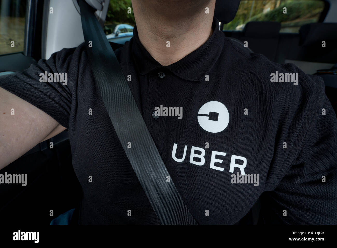 A man wearing a black polo t-shirt bearing the company logo drives an Uber taxi (Editorial use only). - Stock Image